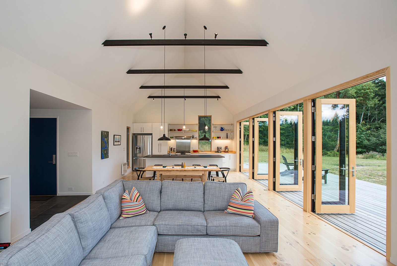 A combination of carefully chosen furniture and finishes, including pine flooring and trim, warms up the lofty white interior. Tagged: Living Room, Sofa, Pendant Lighting, Track Lighting, and Light Hardwood Floor.  The Coyle by Prentiss + Balance + Wickline Architects