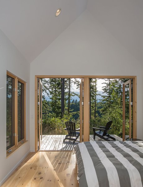 Modern home with bedroom, bed, light hardwood floor, chair, and recessed lighting. In the master bedroom, Douglas firs filter the light and mountain views for a more intimate experience. Photo 6 of The Coyle