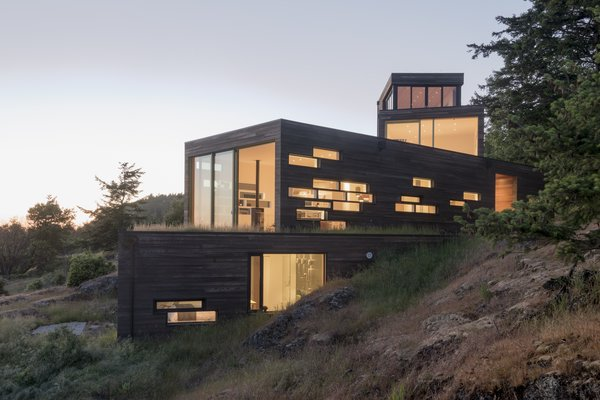 From below, the volumes seem to cascade down the hillside. Windows light up in a dramatic pattern at night, a sharp contrast to their subtle shapes during the day.