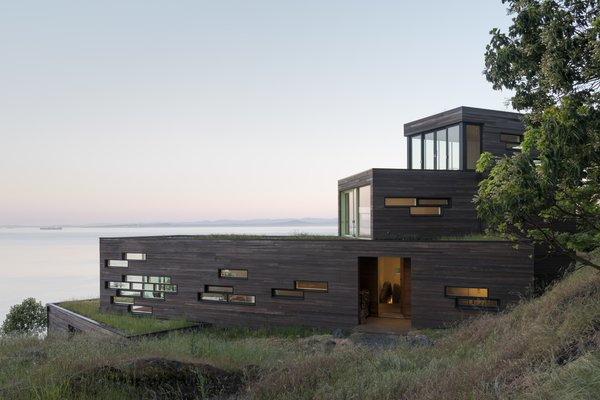 As they follow the slope, each volume shifts slightly to capture different frames of the surrounding water and mountains. Large sliding glass doors provide access to both these expansive views and to green roof patios.