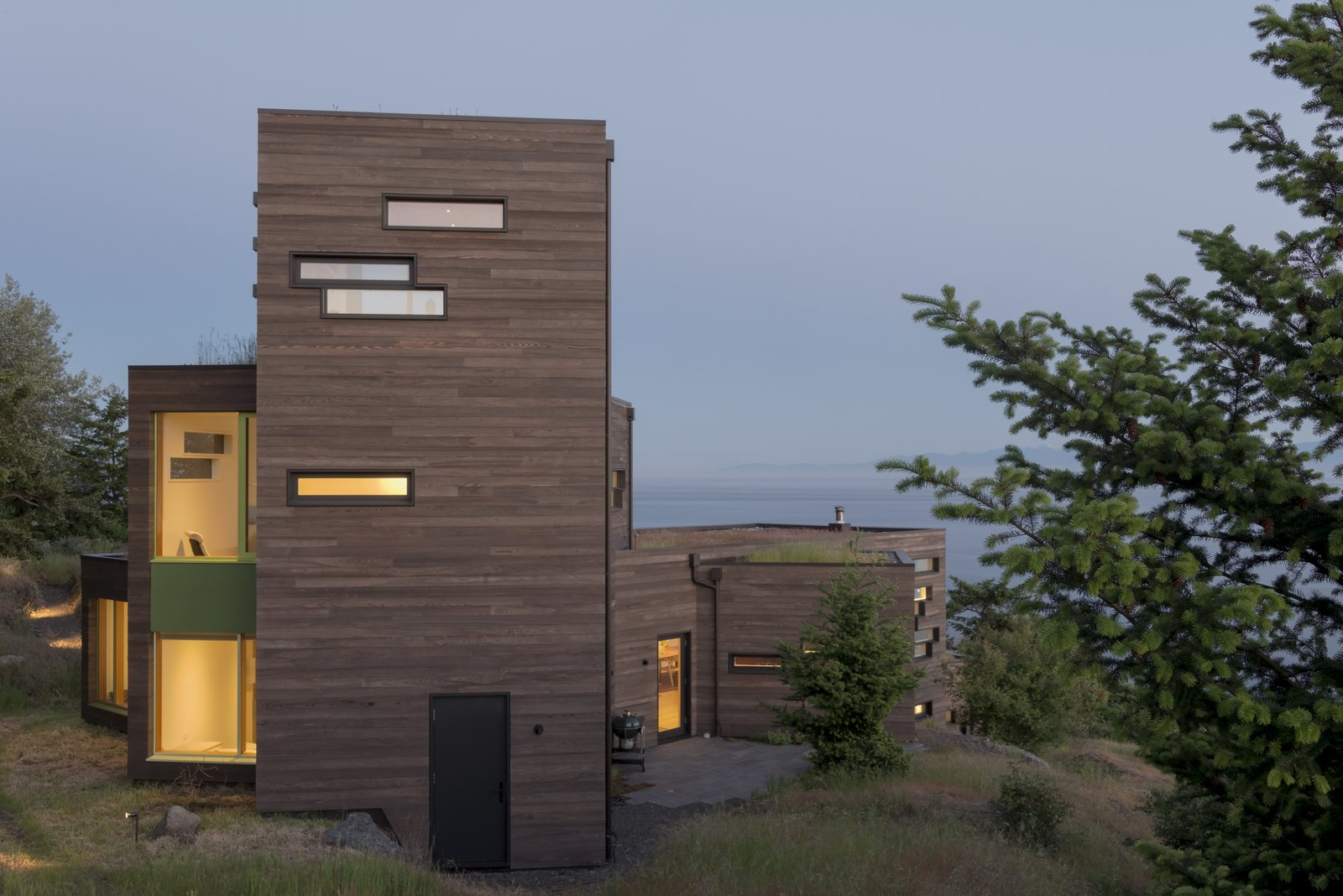 Viewed from the hill above, the structure rises to peer out over the water while firmly anchored back to the ground. Tagged: Exterior, House, Green Roof Material, and Wood Siding Material. Bailer Hill by Prentiss + Balance + Wickline Architects