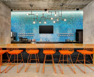 These 6 Collaborative Coworking Spaces Will Give you Serious Office Envy - Photo 8 of 10 - Techspace Austin's vibrant kitchen area features a custom bar designed by DoveTail Custom Woodworks.