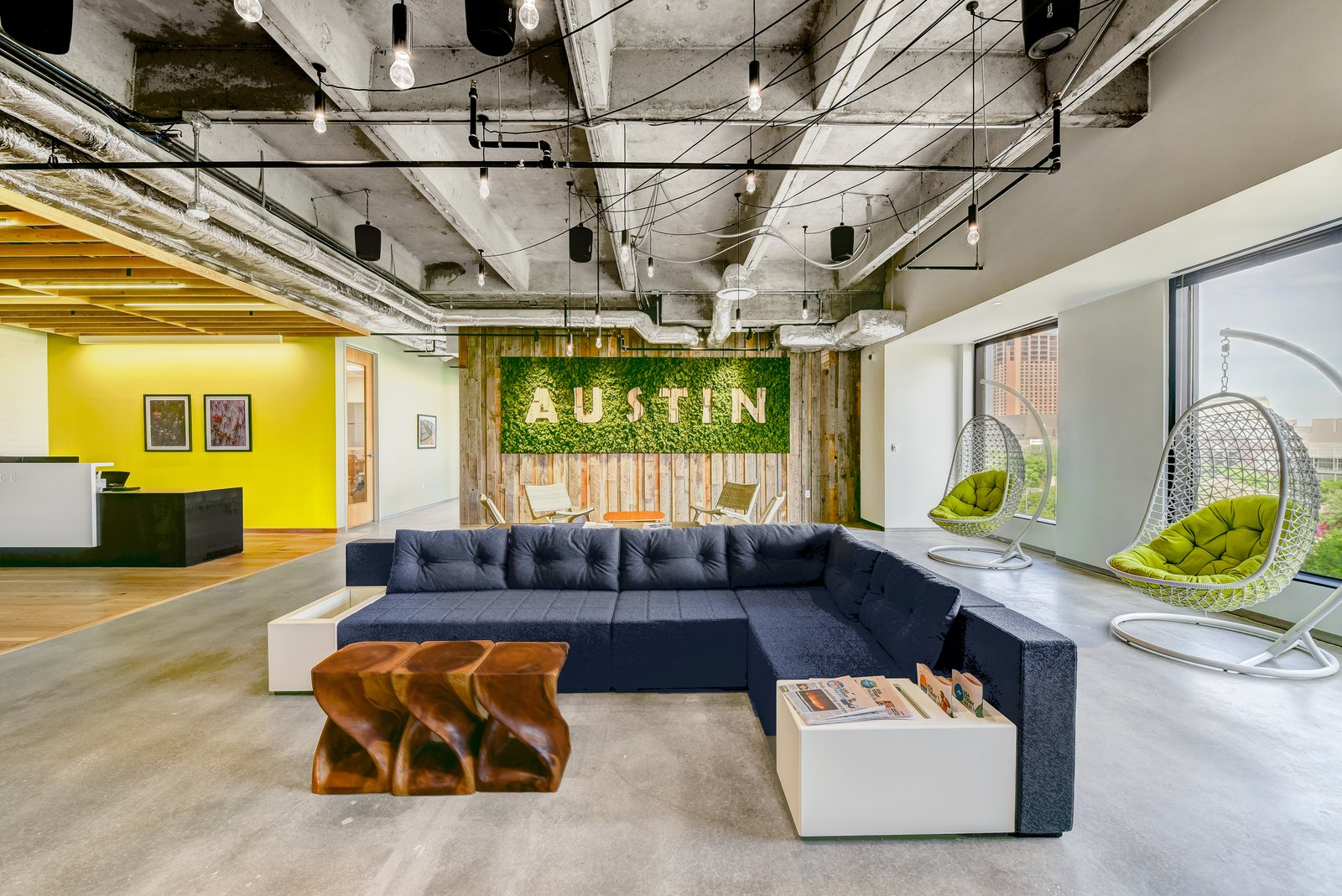 The locally sourced reclaimed wooden wall and moss sign by Articulture bring the outdoors inside in Techspace Austin's office.
