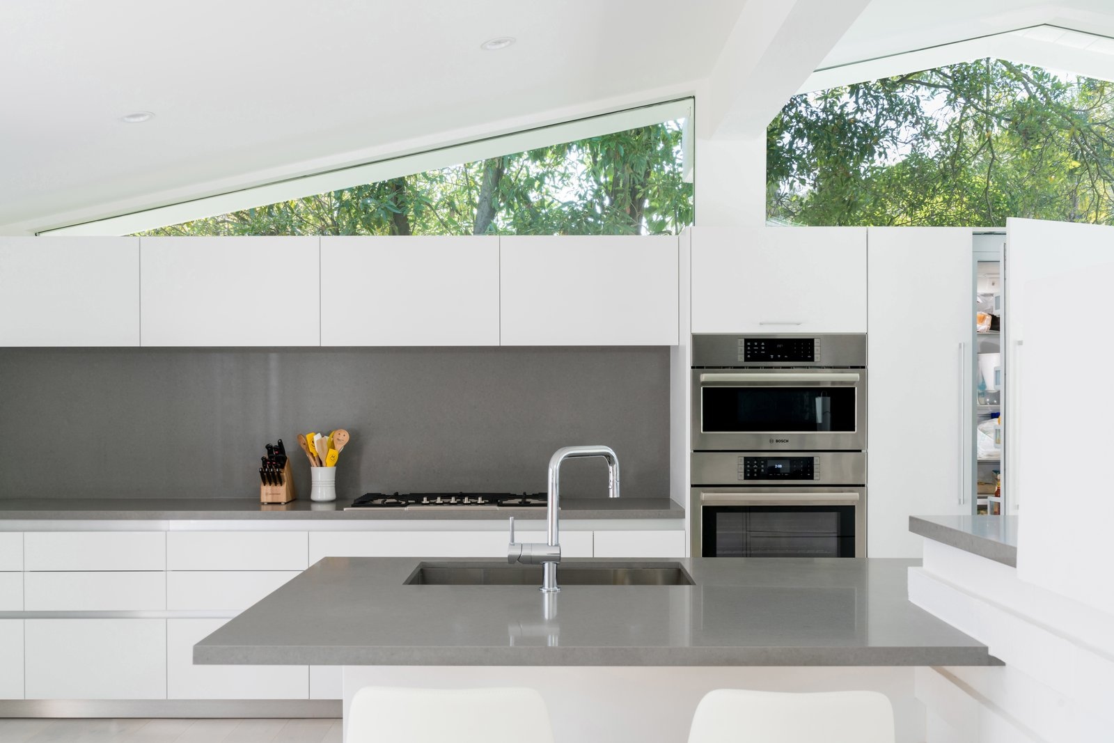 The sleek oven duo, aligned beautifully with clerestories above, sits flush with kitchen cabinetry. Tagged: Kitchen, Engineered Quartz Counter, White Cabinet, Recessed Lighting, Wall Oven, and Undermount Sink. A Breezy Midcentury Renovation in the Hollywood Hills - Photo 3 of 3