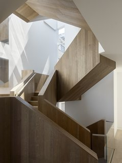9 Unique Stair Railings - Photo 3 of 9 - In a major renovation of a San Francisco townhouse, a striking interior stair crafted of fumed and stained oak panels that clad an asymmetrical sculptural stair. The incorporation of a light well at the top of the stair floods it with light.