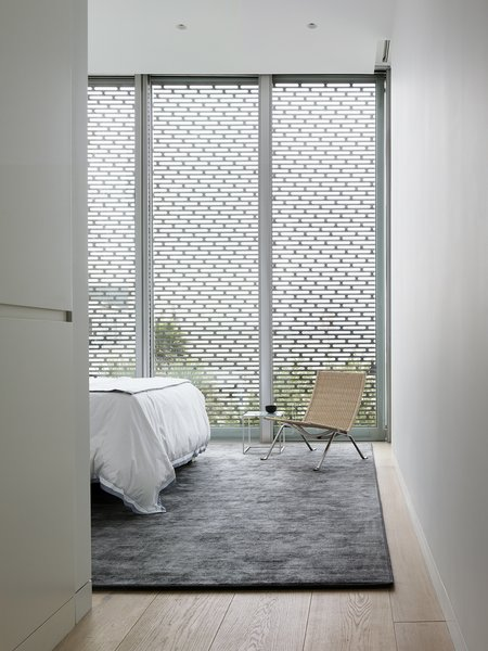 The master bedroom, modest in size, features Stark area rug and Poul Kjærholm PK22 wicker lounge chair.