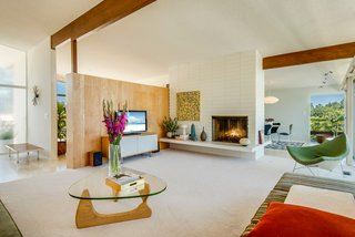 A Midcentury Home For Sale in L.A. That Was Originally Designed For a WWII Pilot - Photo 6 of 16 - Original to the home, the large double-sided fireplace anchors the main floor's living room.