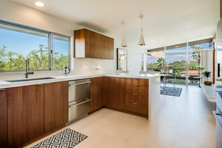 A Midcentury Home For Sale in L.A. That Was Originally Designed For a WWII Pilot - Photo 2 of 16 - The updated kitchen features sleek walnut cabinetry, Fisher & Paykel appliances, Caesarstone countertops with a waterfall edge, and modern pendant lighting.