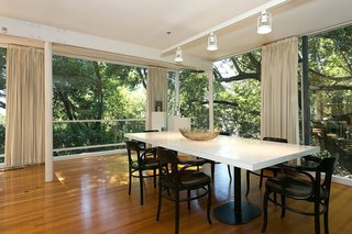 An Amazing Tree-Covered Glass House For Sale in the Berkeley Hills - Photo 3 of 20 - On the main level, the home's dining room is open to the living area and the outdoors.