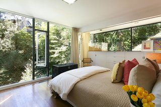 An Amazing Tree-Covered Glass House For Sale in the Berkeley Hills - Photo 16 of 20 - A corner bedroom's floor-to-ceiling windows allow sunlight to stream in, while the mature trees help maintain privacy.