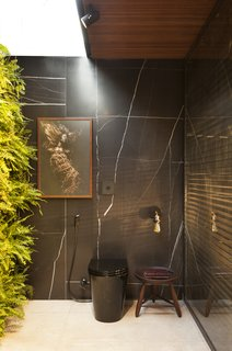 An Incredible Brazilian Home That Celebrates Art, Travel, and Nature - Photo 12 of 14 - The black toilet is nearly camouflaged against the marble-clad walls, while art and greenery stand out.