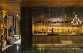 An Incredible Brazilian Home That Celebrates Art, Travel, and Nature - Photo 4 of 14 - The home's kitchen marries a wood-slatted ceiling and wood cabinetry with marble counters.