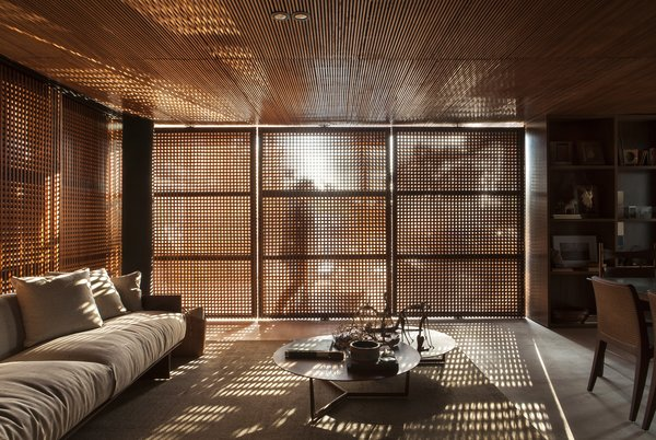 The slatted wood exterior selectively filters sunlight, cooling the interior and creating interesting light and shadow patterns.