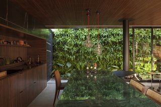 An Incredible Brazilian Home That Celebrates Art, Travel, and Nature - Photo 5 of 14 - Sliding glass walls tuck into the home's stone exterior, allowing the living space to be completely open to the lush vertical garden outside.