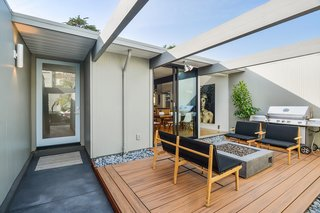 Check Out 2 Beautifully Renovated Eichlers For Sale in San Francisco - Photo 3 of 22 - The entry atrium includes a cozy seating area with a gas fireplace.