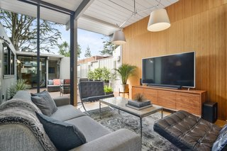 Check Out 2 Beautifully Renovated Eichlers For Sale in San Francisco - Photo 8 of 22 - The inviting living room's floor-to-ceiling windows and glass doors open up to the courtyard for breezy indoor/outdoor living.