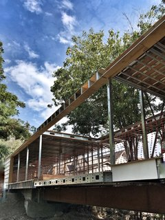Dan Brunn Architecture and Dwell Break Ground on Bridge House in L.A. - Photo 1 of 6 - All on one level, Bridge House spans 210 feet across a stream in Hancock Park, Los Angeles. The structural undertaking was made possible by steel framework fabricated by BONE Structure.