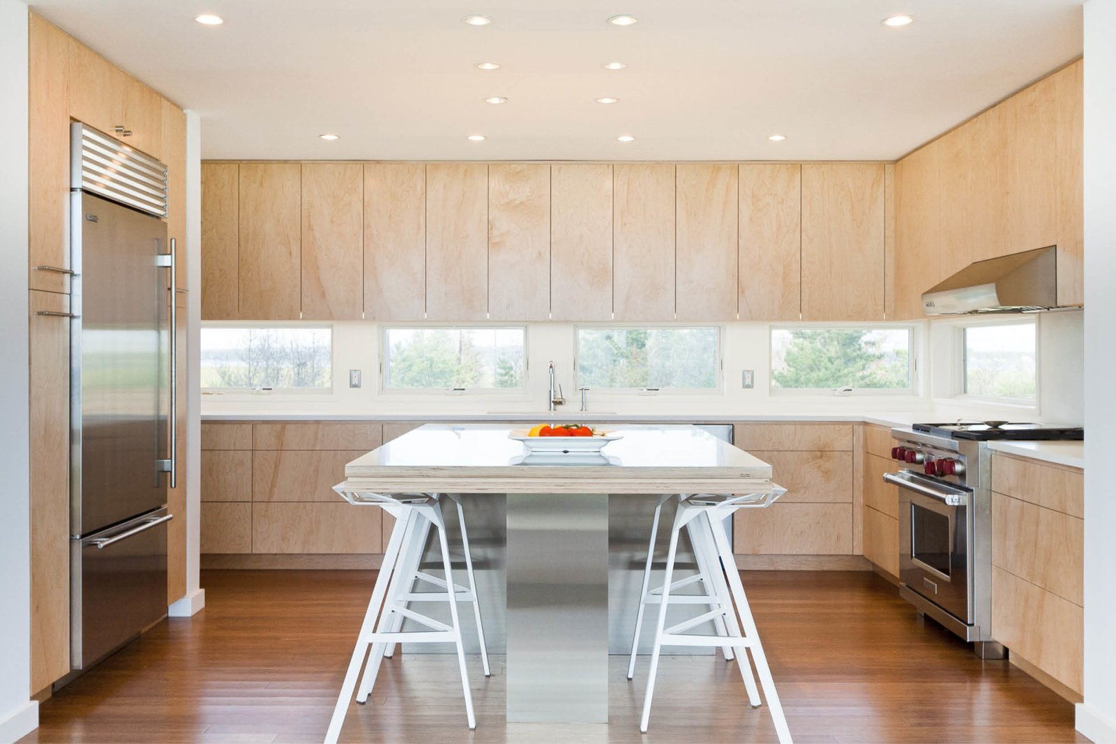 Kitchen cabinets and horizontal slot windows frame views of the bay to the north Tagged: Medium Hardwood, Ceiling, Range Hood, Engineered Quartz, Refrigerator, Wall Oven, Cooktops, Drop In, Wood, Stools, and Dining.  Best Dining Stools Wall Oven Photos from Dune Road Beach House