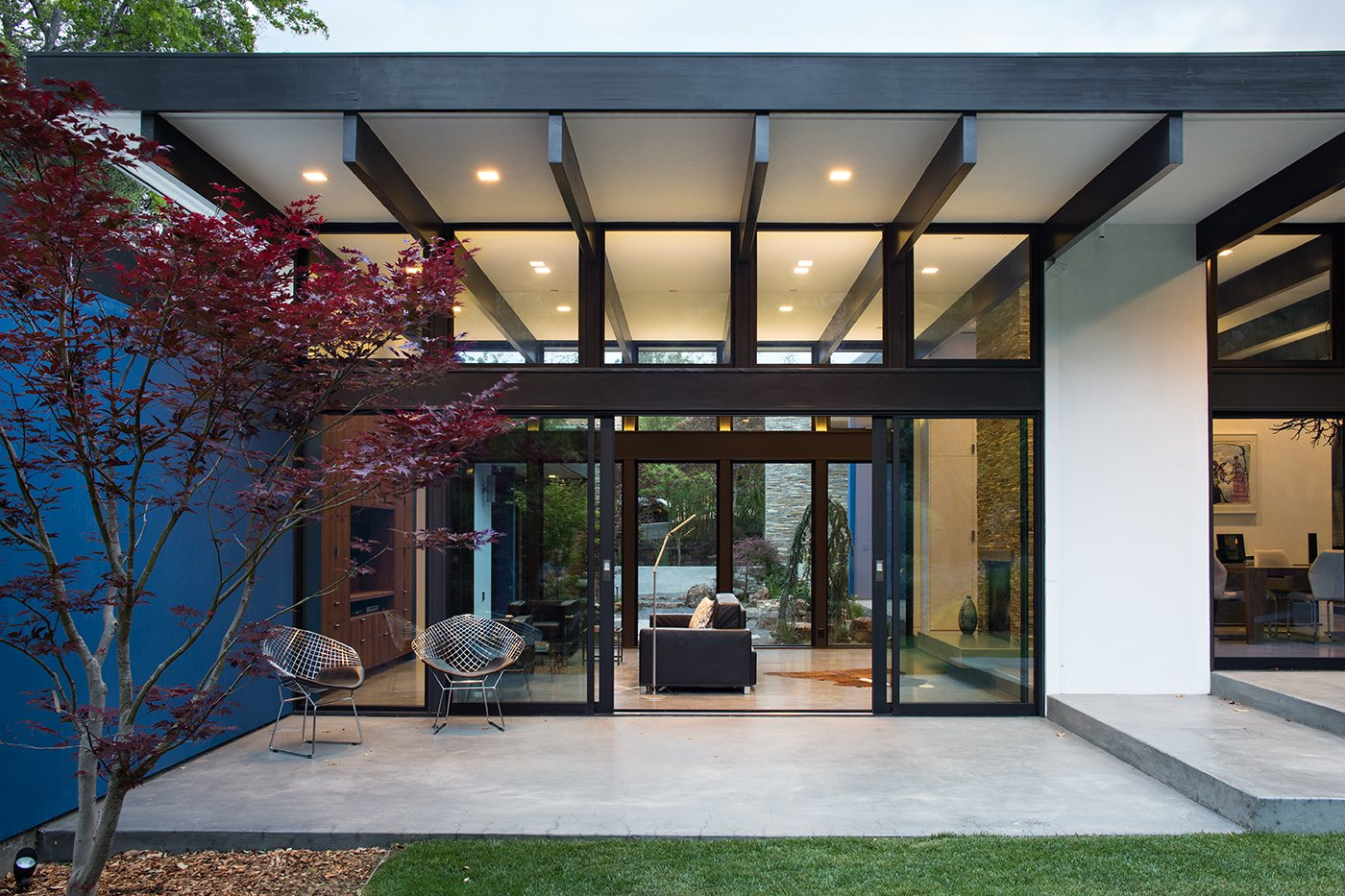 Modern Atrium House  The owners, inspired by mid-century modern architecture, hired Klopf Architecture to design an Eichler-inspired 21st-Century, energy efficient new home that would replace a dilapidated 1940s home. The home follows the gentle slope of the hillside while the overarching post-and-beam roof above provides an unchanging datum line. The changing moods of nature animate the house because of views through large glass walls at nearly every vantage point. Every square foot of the house remains close to the ground creating and adding to the sense of connection with nature. Tagged: Exterior, Mid-Century Building Type, and House.  Klopf Architecture by Klopf Architecture