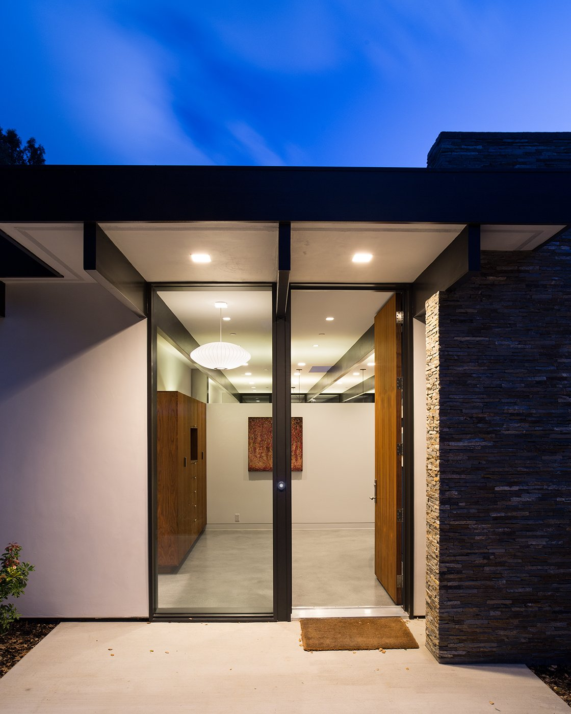 Modern Atrium House  The owners, inspired by mid-century modern architecture, hired Klopf Architecture to design an Eichler-inspired 21st-Century, energy efficient new home that would replace a dilapidated 1940s home. The home follows the gentle slope of the hillside while the overarching post-and-beam roof above provides an unchanging datum line. The changing moods of nature animate the house because of views through large glass walls at nearly every vantage point. Every square foot of the house remains close to the ground creating and adding to the sense of connection with nature.  Klopf Architecture by Klopf Architecture