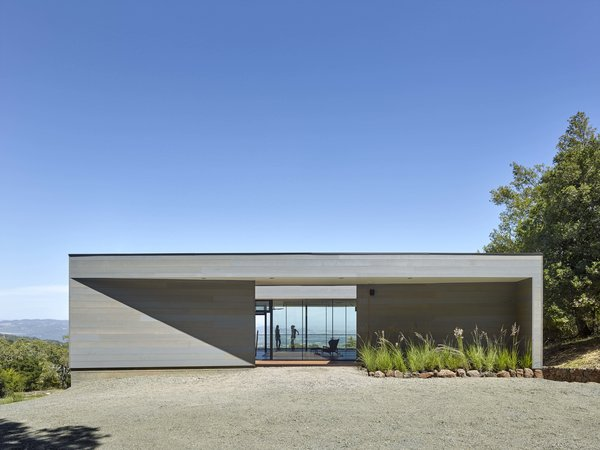 Entry drive looking through courtyard to views beyond. Photo  of Box on the Rock modern home