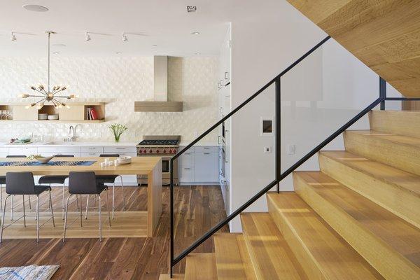 Modern home with dining room, track lighting, dark hardwood floor, bar, pendant lighting, and chair. Photo  of 29th Street Residence