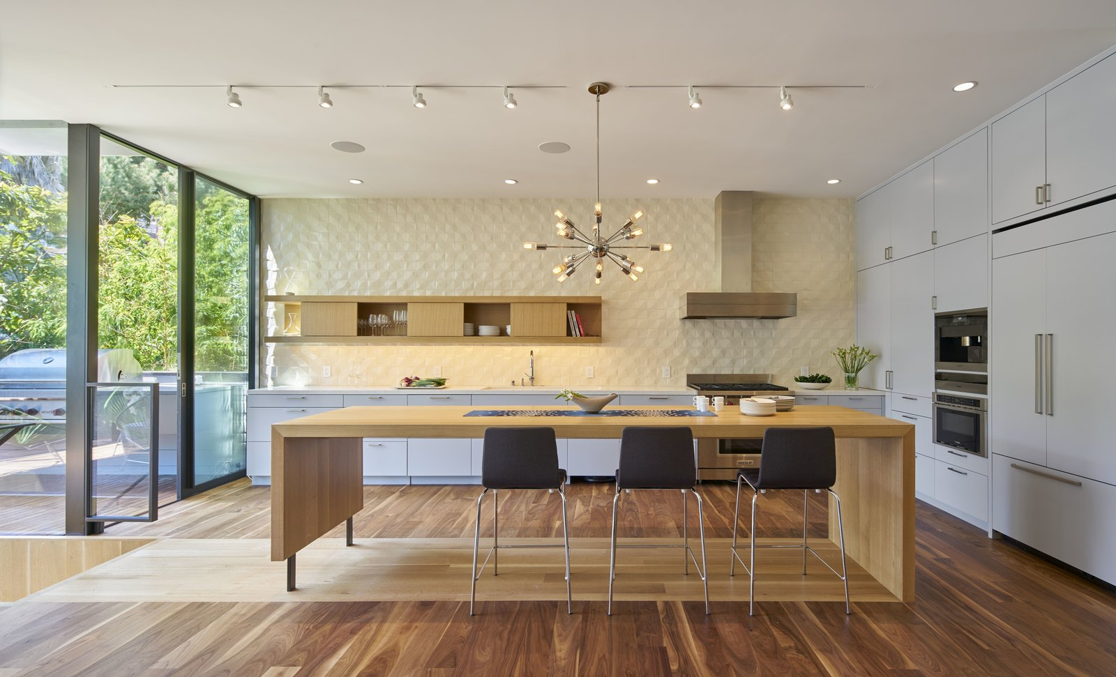 Tagged: Kitchen, Dark Hardwood Floor, Colorful Cabinet, Wood Cabinet, Light Hardwood Floor, Pendant Lighting, Track Lighting, Refrigerator, Wall Oven, Microwave, Range, and Range Hood.  29th Street Residence by Schwartz and Architecture