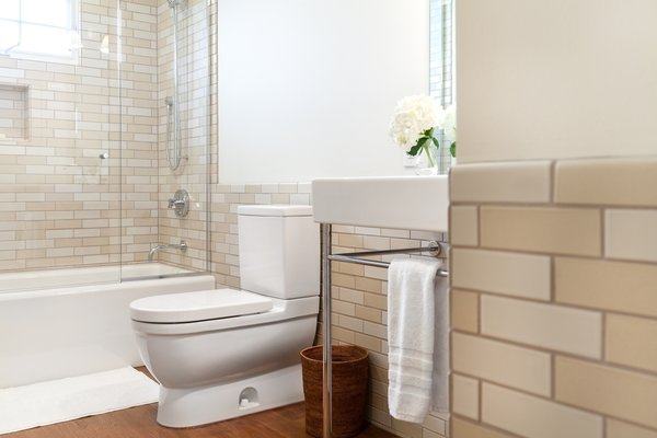 Modern home with ceramic tile wall, medium hardwood floor, pedestal sink, and bath room. Guest Photo 4 of 7th Avenue