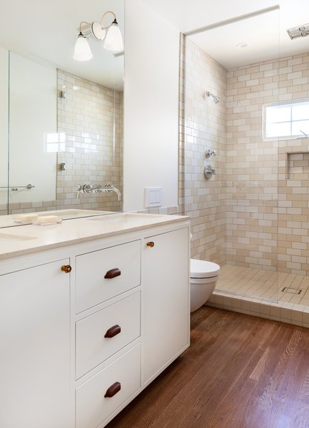 Modern home with marble counter, ceramic tile wall, medium hardwood floor, two piece toilet, wall lighting, undermount sink, bath room, and enclosed shower. Master Photo 7 of 7th Avenue