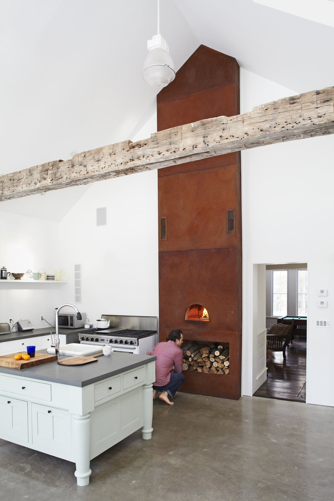 Cor-Ten steel panel tower, acid-oxodized and weathered over three years, houses a wood-burning pizza oven at its base.