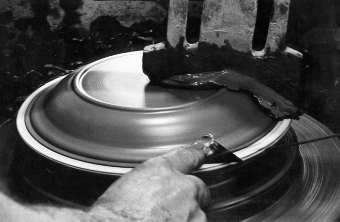 This in an archival photograph showing a plate being formed in the 1950's on a manual jiggering machine.