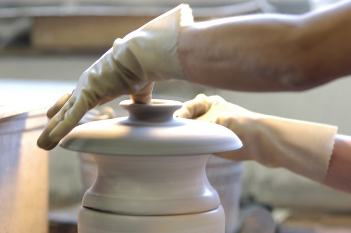 Many details require an addition step. Here, a lid is pulled off the wet clay when it is being formed. This handle is for a casserole lid. There is no mold for this piece, so each finished lid has its own character.  Photo 17 of 36 in Sausalito Dinnerware Factory Tour