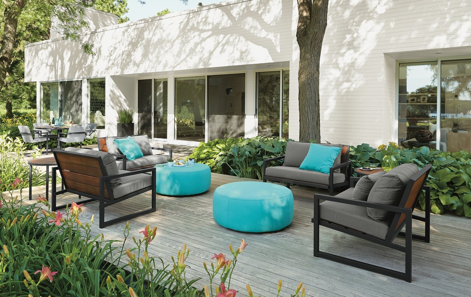 Montego sofa with cushions, Montego lounge chair with cushions, Boyd round ottoman, solid outdoor pillows Tagged: Outdoor, Back Yard, Large Patio, Porch, Deck, Wood Patio, Porch, Deck, Gardens, and Shrubs.  Photo 8 of 8 in Expert Design Advice: Outdoor Dining Spaces