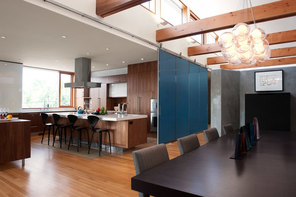 DECA Architecture designed a moveable wall to create a guest area when closed, and join the space with the kitchen and dining room when open. Photo 2 of The CYRK Building modern home
