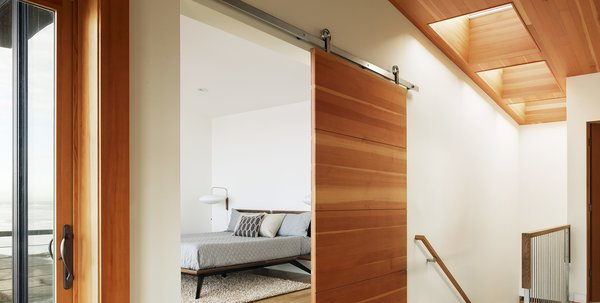 An oversized door panel on the Baldur sliding door hardware system separates the living room and bedroom. Photo 3 of The Road's End House modern home