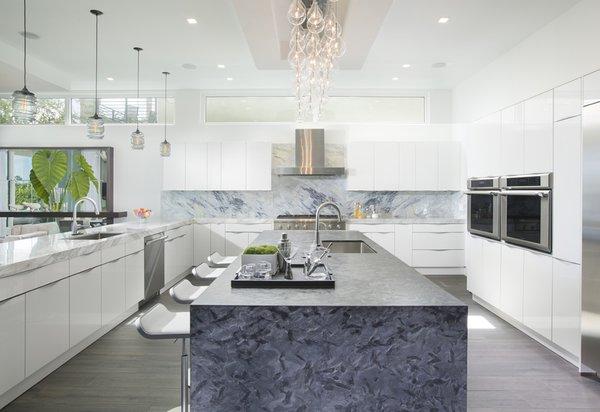 Modern home with kitchen, marble counter, pendant lighting, white cabinet, and dark hardwood floor. Photo  of Santa Barbara Estate