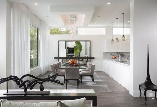 Modern home with kitchen, marble counter, white cabinet, dark hardwood floor, and pendant lighting. Photo 2 of Santa Barbara Estate