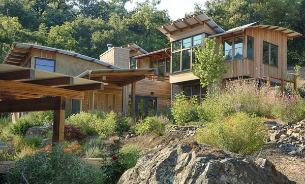 The homestead is designed as a series of east-west running volumes, roughly paralleling the topography and stepping up the hill. Boulders discovered during excavation were located throughout the gardens. Photo 13 of Healdsburg Family House modern home