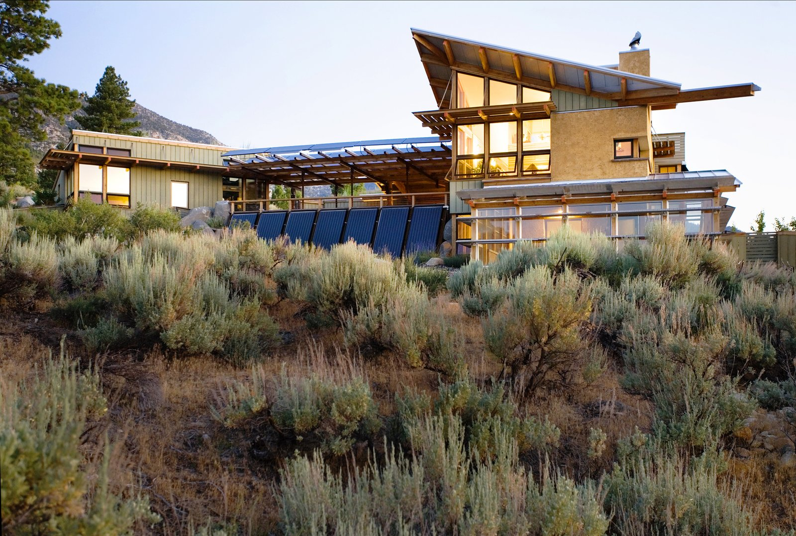 The earth finish, slatted cement board siding, and metal roofing harmonizes with the landscape and take advantage of the changing desert light.