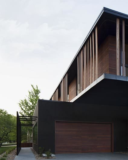 Details like vertically oriented wood siding, straight-forward forms, and overhanging masses were motivated by this modernist aesthetic. #exterior #bauhaus #wood #kansascity #baulinderhaus #hufft  Photo credit by Mike Sinclair  Photo 4 of BauLinder Haus modern home