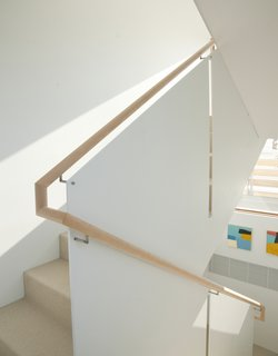 9 Unique Stair Railings - Photo 2 of 9 - In a narrow house in the Chesapeake Bay, a stair railing consists of warm wood in contrast with thin, powder-coated panels of steel with exposed steel fasteners. The round, projecting handrail provides a comfortable grip for visitor's hands, and the white panels keep the railing feeling light and bright.