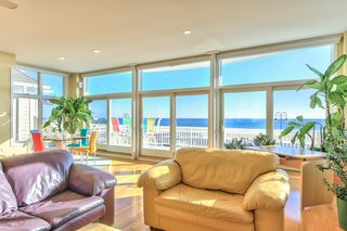 Coastal Contemporary:  10 Modern Seaside Homes - Photo 2 of 10 - Captivating Oceanfront Home: Sit back and enjoy the captivating panoramic oceanfront views from this custom-built contemporary estate in Belmar, New Jersey. An open design concept showcases the grand views with floor to ceiling areas on the second and third levels. Presented by Ward Wight Sotheby's International Realty.