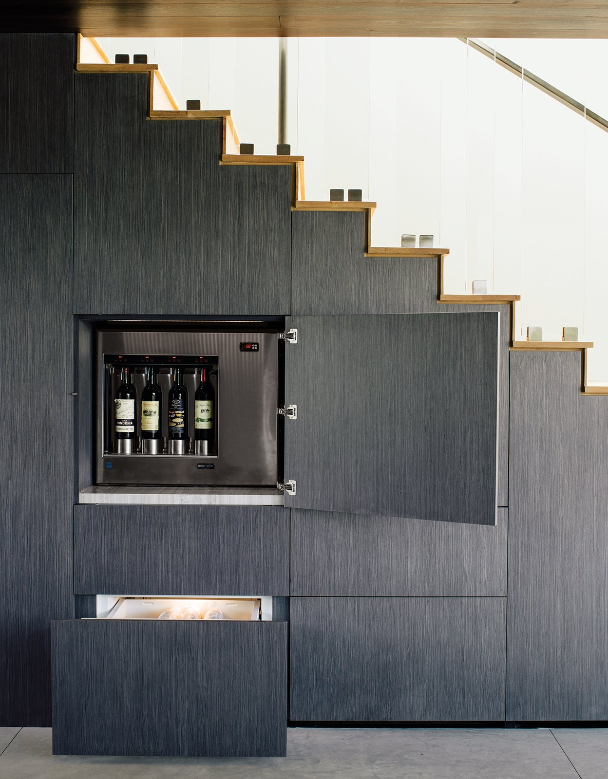 Photo caption: The wall beneath the stairs of this Beverly Hills home holds hidden storage, including an Enomatic wine dispenser and Sub-Zero refrigerated drawers. 10 Clever Ways to Sneak Storage Into Your Renovation - Photo 8 of 10
