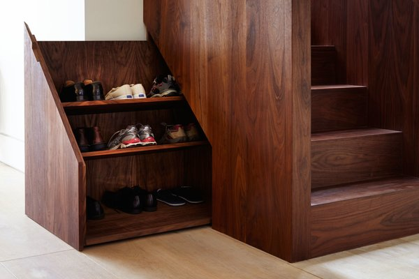 The base of the stairwell includes a hidden compartment to conveniently store shoes.