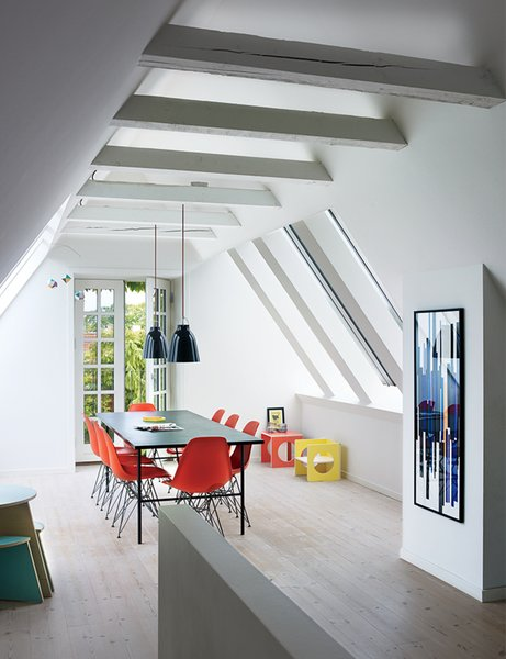 A cramped attic was transformed into a sunny dining room with Vitral windows and white-tinted pine floors by Dinesen. The Sara table is by Hay, the Shell chairs are by Charles and Ray Eames, and the artwork is a hand-printed textile which has been framed.