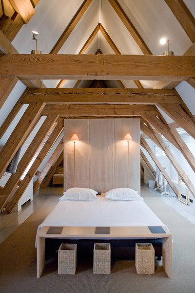 Giant wooden roof beams in the attic suite add to the peaceful and minimalist space.