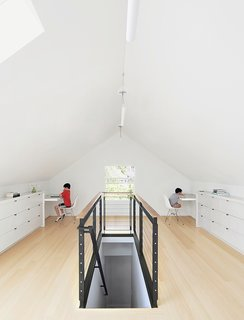 10 Bright and Airy Modern Attic Renovations - Photo 10 of 10 - Bamboo flooring and custom built-ins—fashioned from medium-density fiberboard with a white-lacquer finish—brightened the 650-square-foot attic. The custom-designed  blackened-steel balustrade has cable inserts and a walnut handrail.