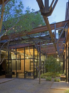 "9 Inspirational Examples of Adaptive Reuse - Photo 5 of 9 - Armstrong Oil and Gas in Denver, Colorado. Designed by Lake|Flato Architects. Winner of the 2011 Institute Honor Award for Interior Architecture. Project description: ""The adaptive re-use of a 1900s machine shop celebrates the spirit, craft and materiality of its original program. The transformed spaces are organized around a new landscaped courtyard created by stripping away the center section of the existing roof to bring in natural light and ventilation to the interior spaces. A gated entry court on the street front acts as a threshold to the courtyard framed by two brick volumes containing the building's public spaces on one side and office spaces on the other."""