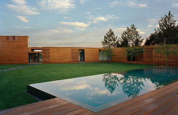 """As the facade of a Bates Masi-designed home in Water Mill, New York, rises from 8 to 14 feet high, the mahogany planks subtly widen. """"It was quite a demand to make of the contractor,"""" architect Paul Masi says. """"But the design was so much about traveling through the site and weaving [the house] together with the deck."""""""