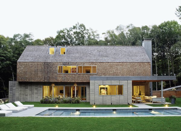The gabled house, constructed from precast-concrete panels by Superior Walls with wood framing, offers a pared-down version of a traditional New England silhouette. The exterior cedar paneling also appears on the ceiling of the custom-built chef's kitchen inside.